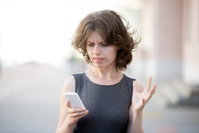 Woman looking at phone with a confused expression.