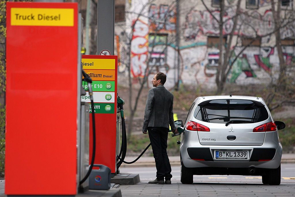 A man watches a fuel pump as he fills his car at a gas station.