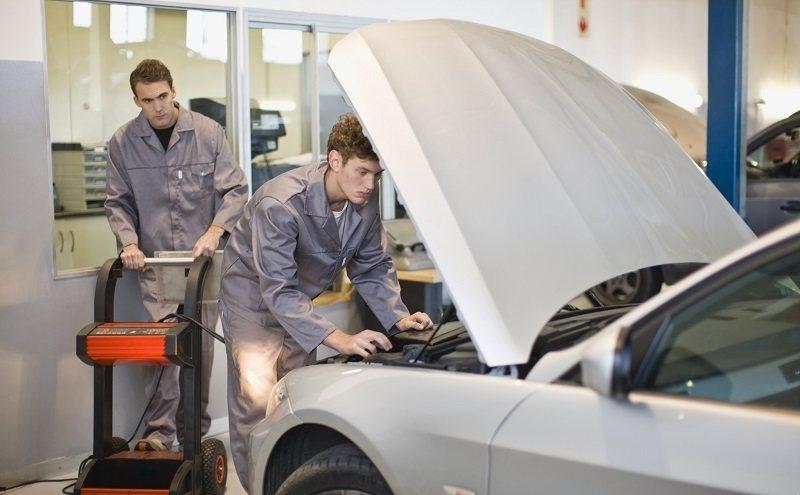 Mechanics working on car engine