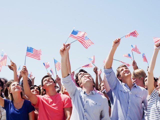 Smiling people waving American flags and looking up in crowd