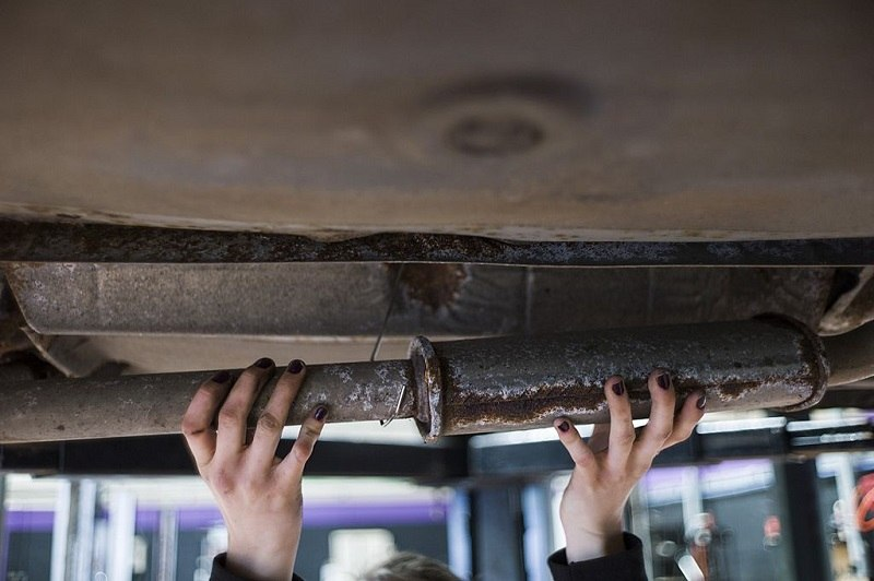 A woman mechanic fixes a car exhaust pipe as she works in an innovative garage and auto repair workshop catering exclusively to female customers, in Saint-Ouen-l'Aumone, in the suburbs of Paris, on May 14, 2014. Inspired by a similar business venture in the southern French city of Montpellier, the garage offers women an alternative to the often heavily male-dominated and macho environment of most auto repair shops, proposing them hands-on, informative classes on mechanics, and even a massage or a manicure during their waiting time.