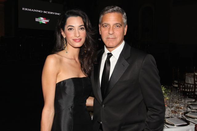 George and Amal Clooney wearing black and posing with their arms wrapped around each other.