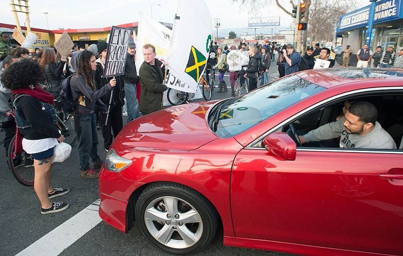 Protesters block traffic as an angry driver honks during an anti-police brutality march in Oakland on January 17, 2015. About hundred protesters disrupted traffic and chanted as they made their way to Oakland Police Station where at least five people were arrested.