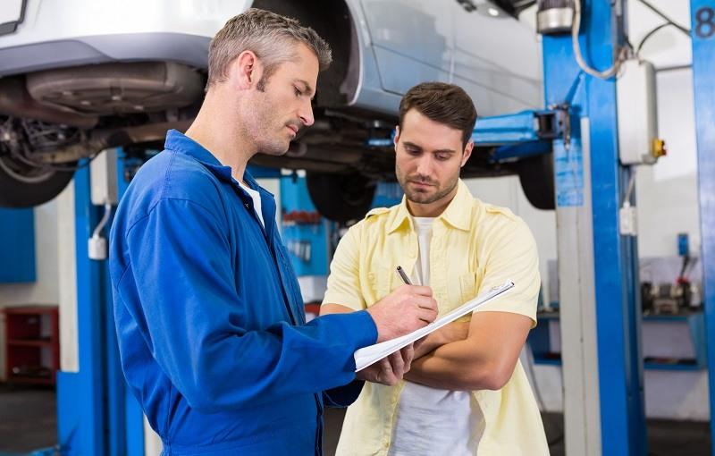 Customer listening to his mechanic at the repair garage