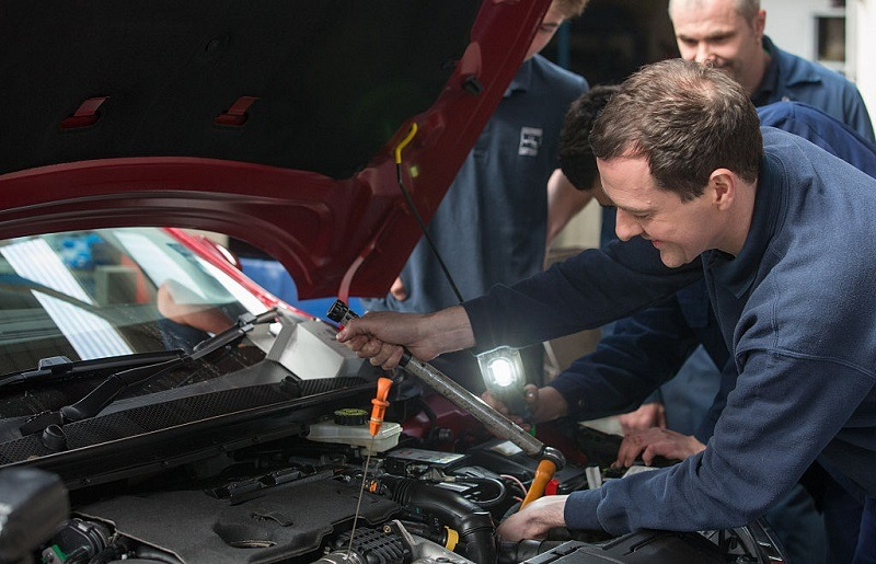 ST AUSTELL, ENGLAND - APRIL 09: Chancellor George Osbourne (R) works under the bonnet of a car that is being serviced in the service and repair workshops as he meets apprentices at Hawkins garage near St Austell on April 9, 2015 in Cornwall, England. Campaigning continues in what is predicted to be Britain's closest national election, which will take place on May 7.