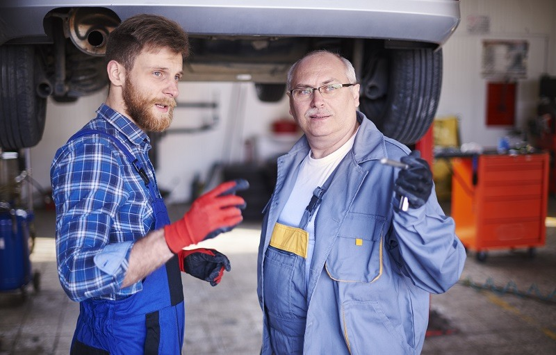 Two mechanics talking in auto repair shop