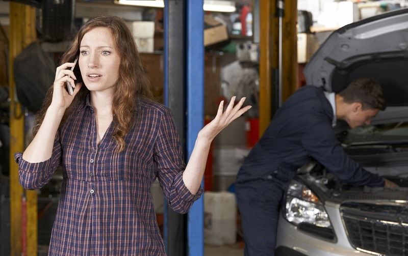 Frustrated Female Customer On Mobile Phone At Auto Repair Shop
