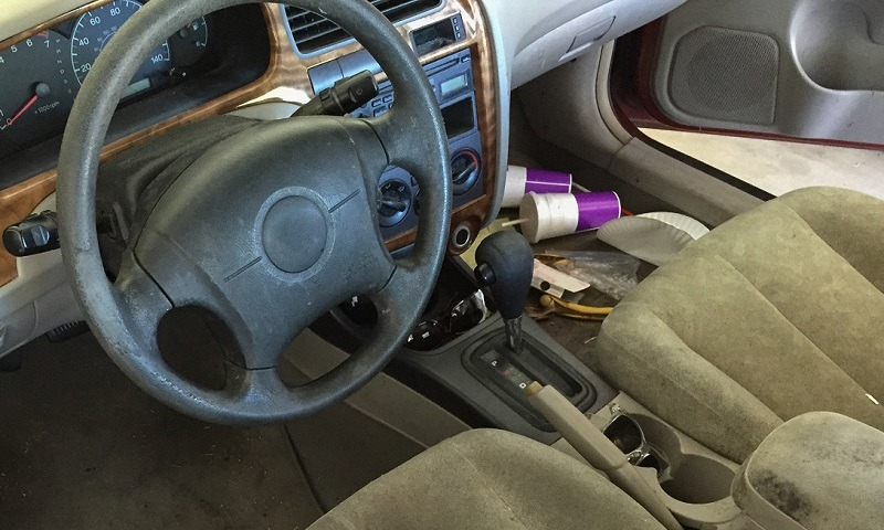 Run Down Car Interior, car cabin cluttered with fast food cups and trash showing run down fabric and faux leather trip of stirring wheel and dirty dashboard console