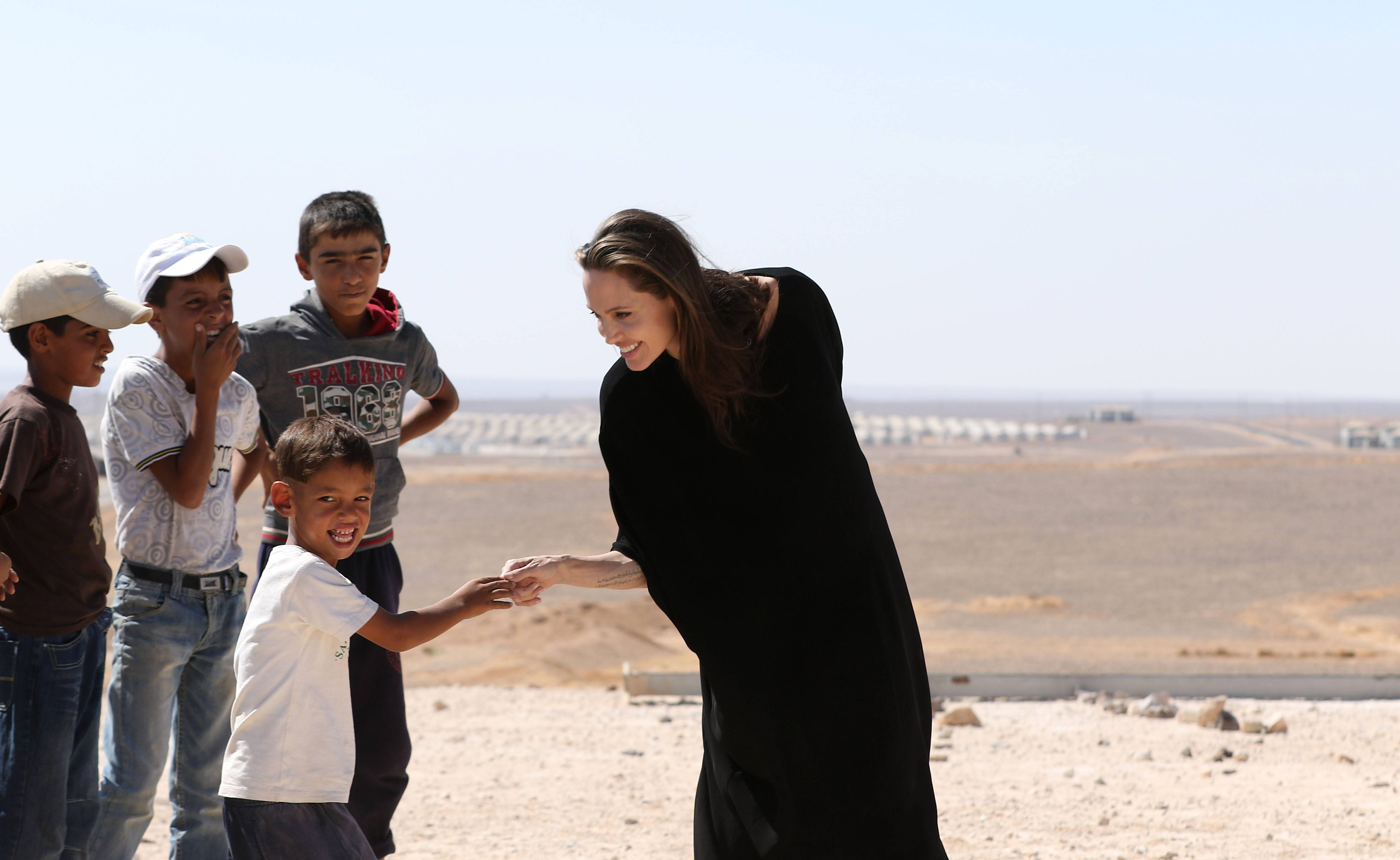 Angelina Jolie talks to children during a visit to a Syrian refugee camp in Azraq