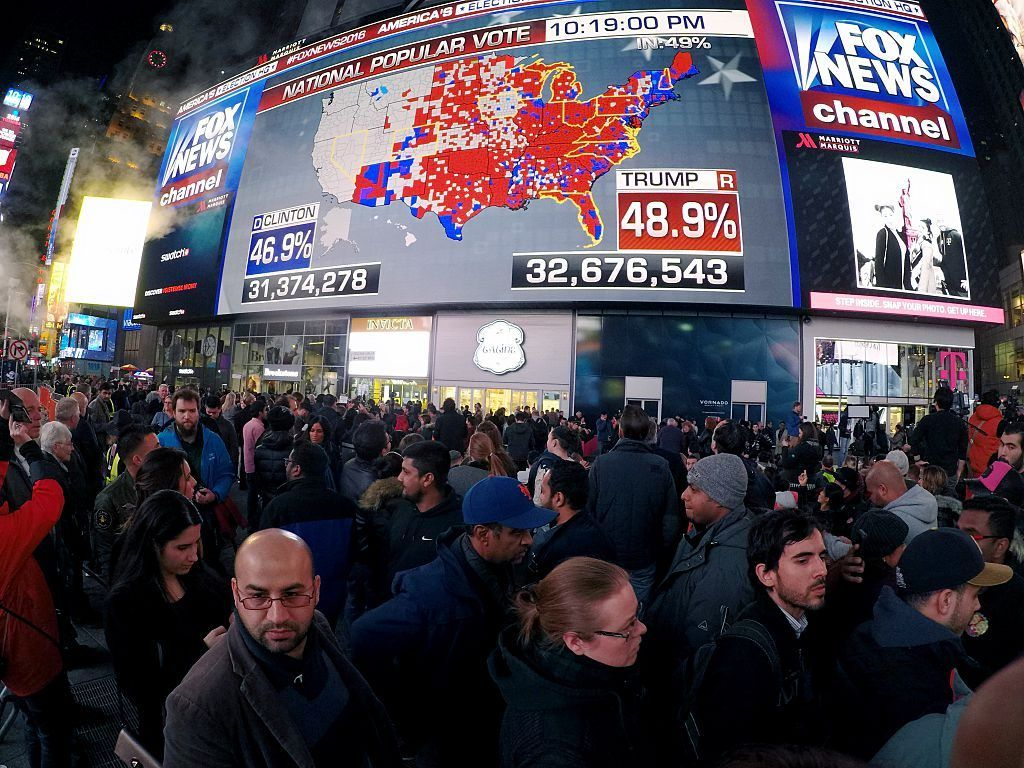 Times Square filled with people at night as the results of the 2016 presidential election are shown on screen