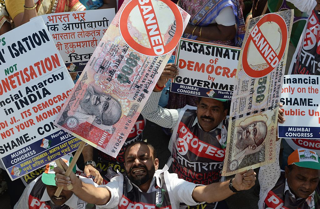 An Indian protester holds placards of banned 500 and 1000 rupee notes during a protest
