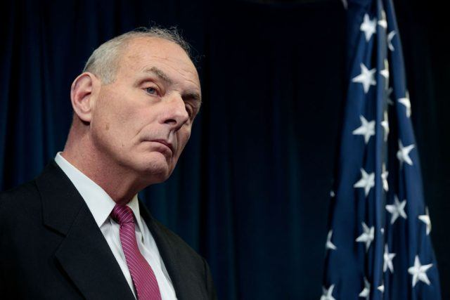 White House Chief of Staff John Kelly standing in front of a flag.