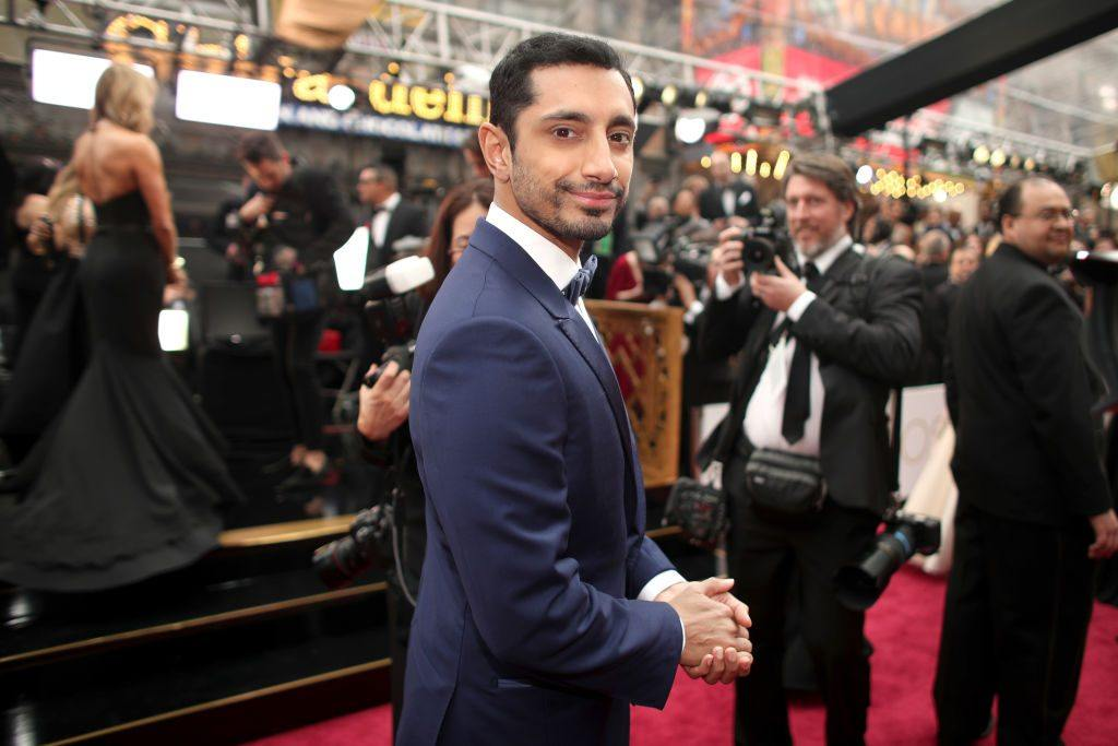 Riz Ahmed on the red carpet at the Oscars surrounded by cameras