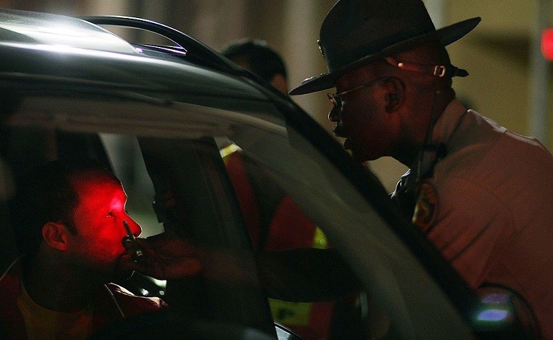 MIAMI - JULY 04: Florida Highway Patrol trooper Raymond Addison checks the eyes of a driver at a DUI traffic checkpoint June 4, 2007 in Miami, Florida. Several law enforcement agencies were conducting the checkpoint and conducting saturation patrols to help save lives during the 4th of July holiday. The National Safety Council has rated the July 4th holdiay as one of most lethal holidays for drivers, with alcohol factoring into nearly half of all motor vehicle deaths.