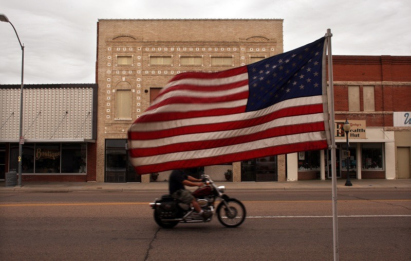 """SIDNEY, NE - JUNE 26: A man rides his motorcycle down a flag laden street June 26, 2007 in Sidney, Nebraska. When rural America was chronicled 50 years ago by Jack Kerouac in his autobiographical novel """"On the Road"""", it was an America full of promise and economic potential, where the majestic openness of the land was entwined with the cult of the automobile. Today, partly due to the loss of the independent family farm, rural America is a state of economic and demographic decline. Despite these changes since Kerouac and his friends sped across the vast American night, much of the visual landscape of the rural United States has remained the same."""
