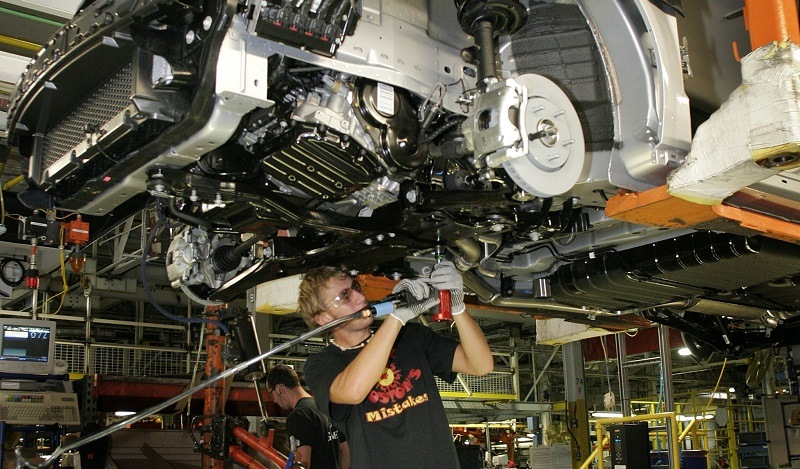 An assembly line worker installs front brake line brackets on new 2008 minivans, the Chrysler Tow & Country and the Dodge Caravan at the Windsor Assembly Plant August 21, 2007 in Windsor, Ontario, Canada.
