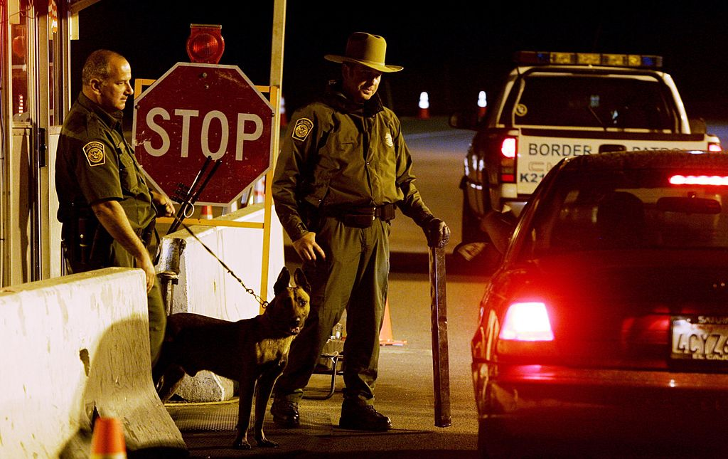 Customs and Border Patrol agents prepare to question a motorist at a checkpoint
