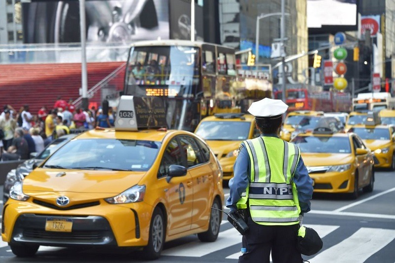 A police officer controls the traffic in Times Square, downtown Manhattan, on July 1, 2017 In New York.