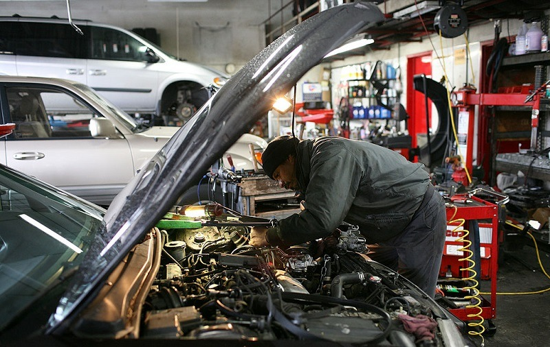 SAN RAFAEL, CA - JANUARY 05: Mechanic Antonio Ramos works on a car at San Rafael Firestone January 5, 2009 in San Rafael, California. According to a survey by the Automotive Service Association, sales at auto repair shops increased 16 percent in November as people make a small investment by way of repairs and maintenance to extend the life of their cars instead of buying a new one.