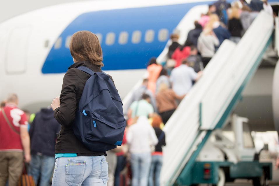 Young woman passenger in 20s travelling with backpack, boarding airplane