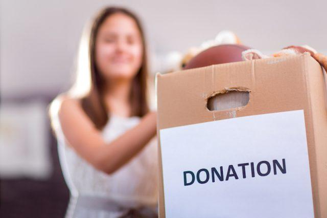 A woman holds a box full of things she will be donating.