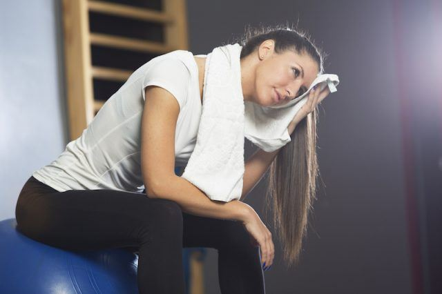 A woman sits on a medicine ball while wiping her face.
