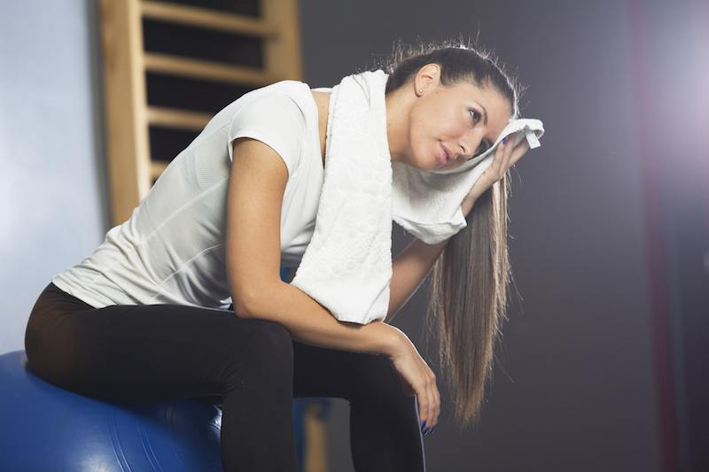 woman wiping her sweat at the gym
