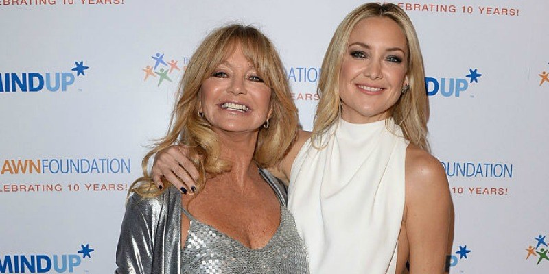 Goldie Hawn and Kate Hudson are smiling and posing together on the red carpet.