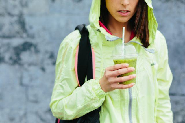 A woman holds a green smoothie while wearing a backpack.