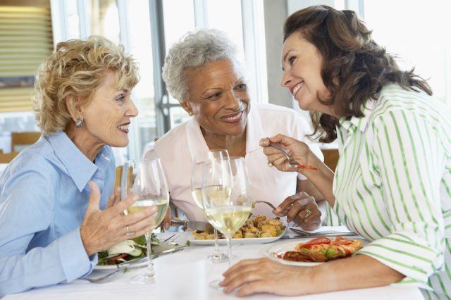 Elderly friends enjoy dinner together