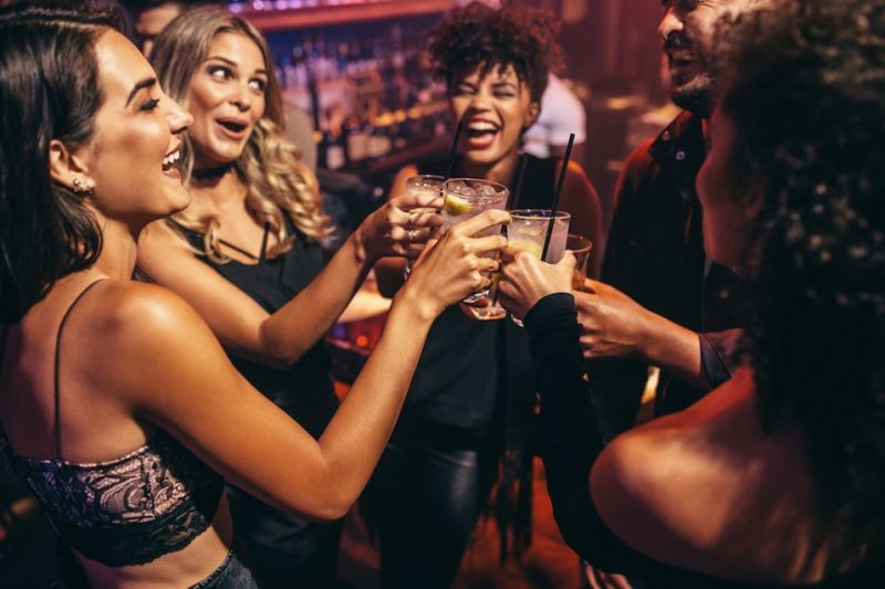 Group of friends partying in a nightclub and toasting drinks.