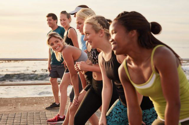 A group of people exercising outside together.