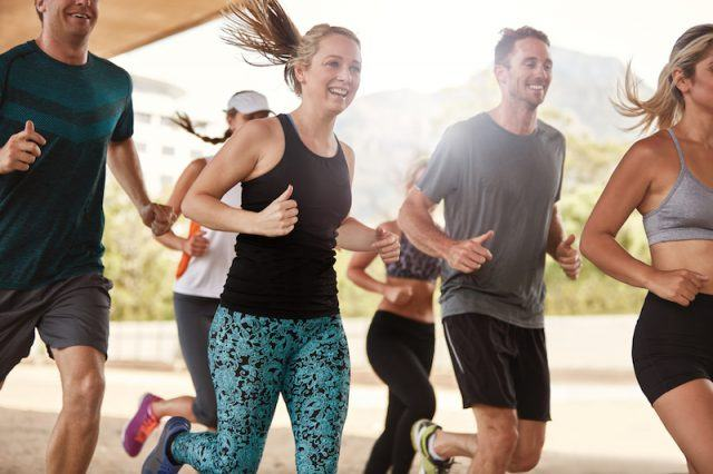 A group of people jog together outdoors.