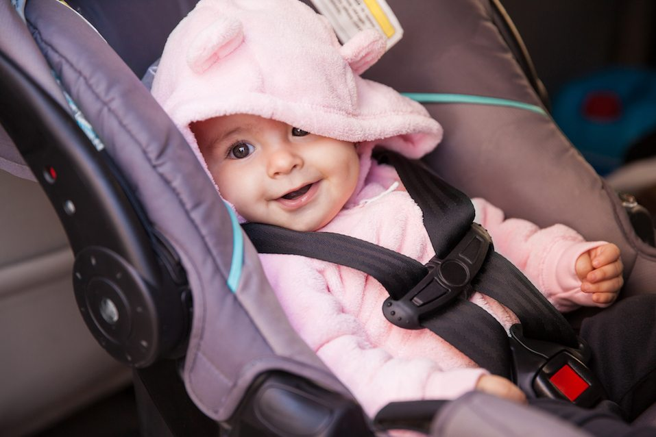 baby girl sitting on a car seat and smiling