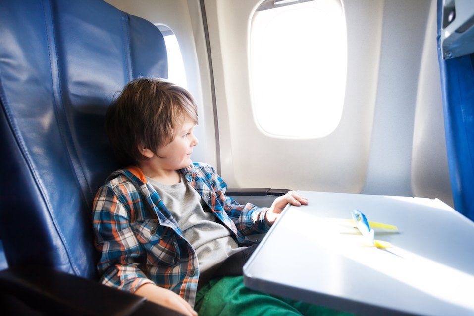 Happy boy sit in plane with toy model on table