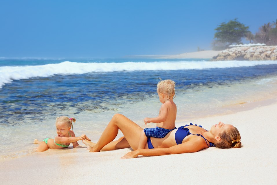 Happy family lying on sand beach and look at sea surf