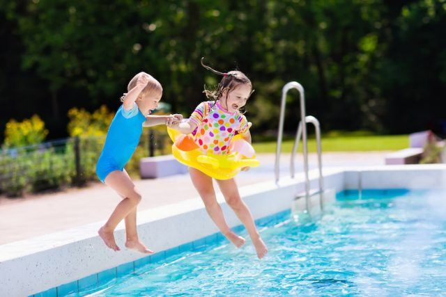 Happy little kids jumping into swimming pool.