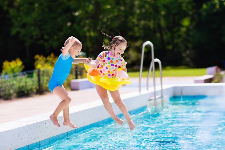 Happy little kids jumping into swimming pool