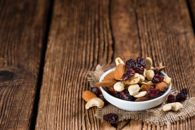 A white dish full of a handful of trail mix on a wooden table