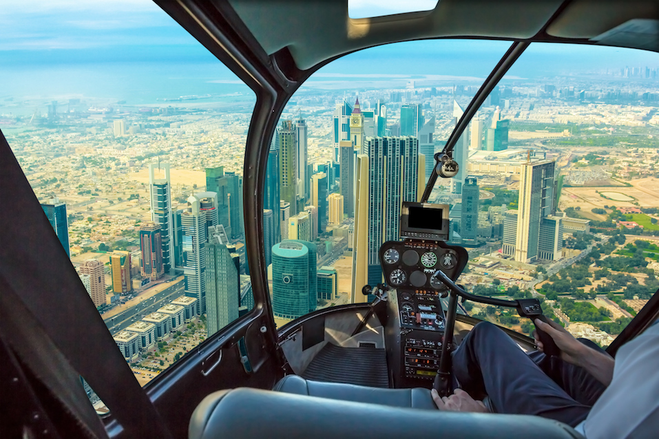 Helicopter cockpit flies in skyscrapers of Dubai downtown skyline