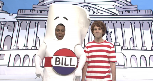 A man dressed up as a governmental bill stands next to another man.