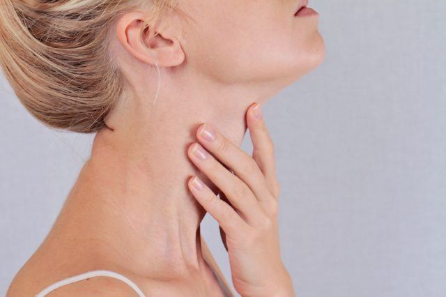 Woman touching her throat where her thyroid gland is