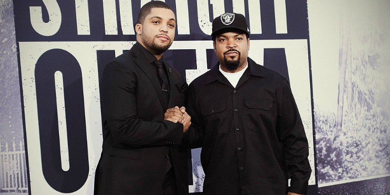 Ice Cube and O'Shea Jackson Jr. are holding hands while posing in black clothes on the red carpet.