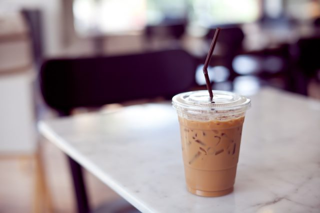 An iced coffee on a white table.