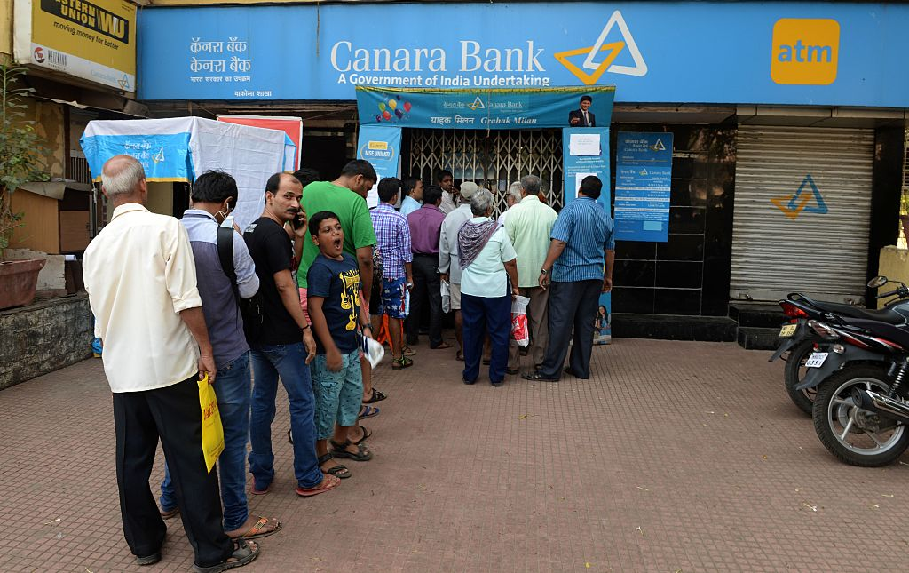 Indian customers queue outside a bank