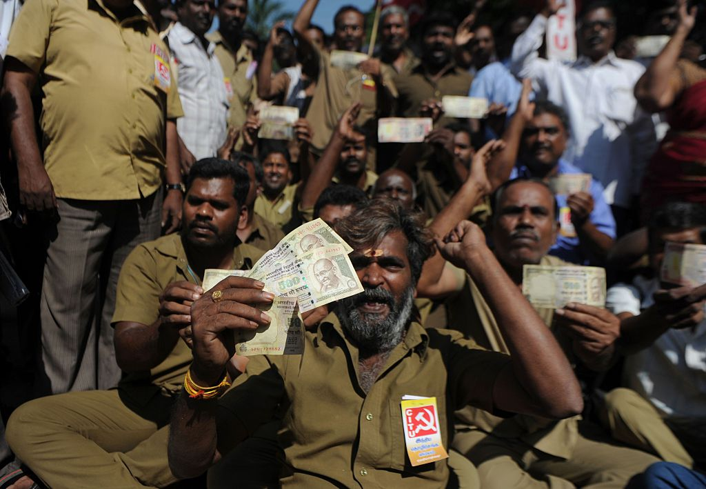 Indian trade union members pose for media holding banned currency notes