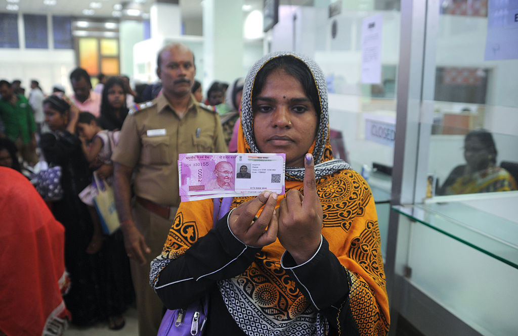A woman from India poses with new 2000 rupee notes