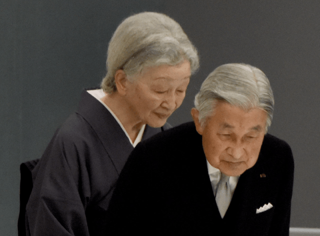Japan's Emperor Akihito and Empress Michiko bow to their guests during a ceremony.