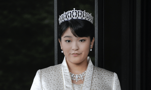 Princess Mako stands in a white suit and a crown.