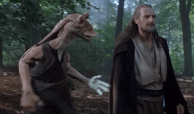 Jar Jar Binks talks to Qui-Gon Junn while walking through a forest.